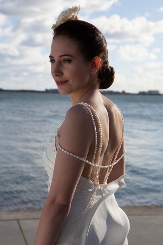 Brudekjole med perler og og smuk flæse og syet rose i håret.