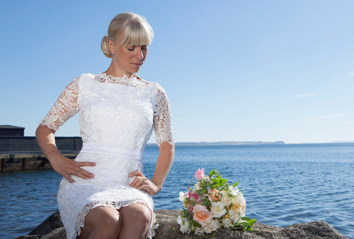 Kort brudekjole i blonde og med baelte ved den permanente