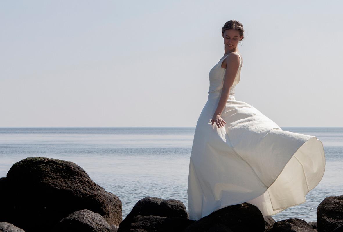 Brudekjole med sus i skørterne på Moesgaard strand.