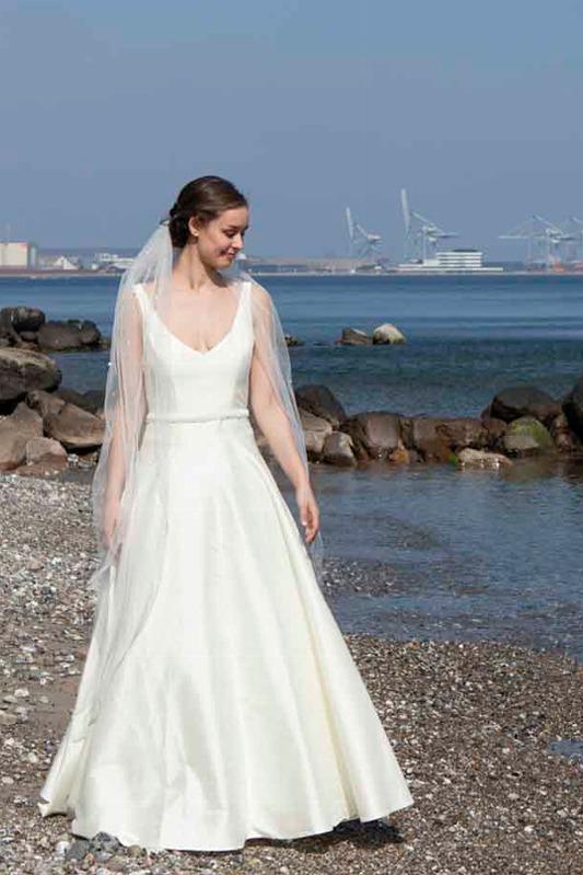 Brudekjole med perlebælte og dyb udskæring på moesgaard strand