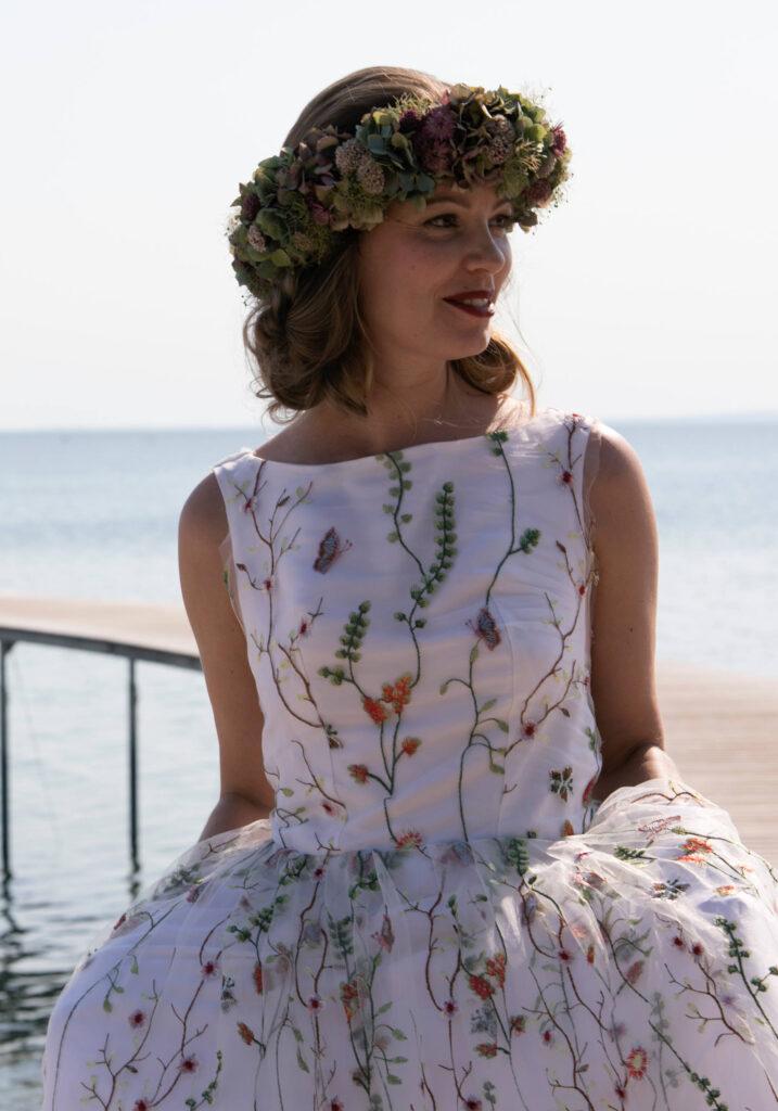 smuk brudekjole med bådudskæring i blonde med smukke farvede blomster og sommerfugle