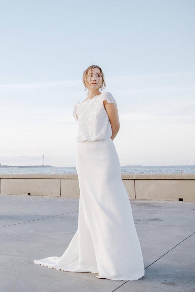 Elegant brudekjole med moderne detaljer og overdel i blonde samt et smukt tætsiddende skørt med kort slæb