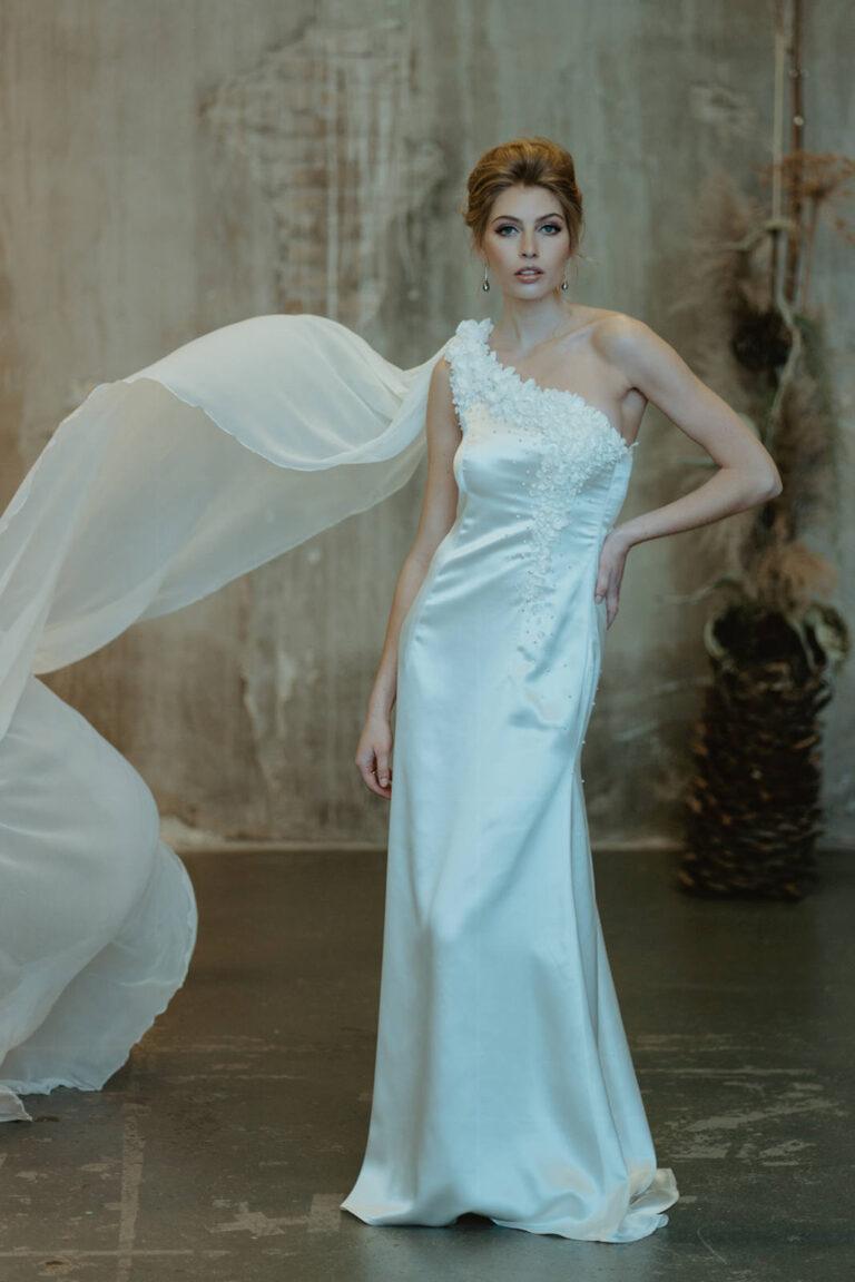 unik brudekjole med silkeblomster påsyede med perler og lang flæse fra skulderen