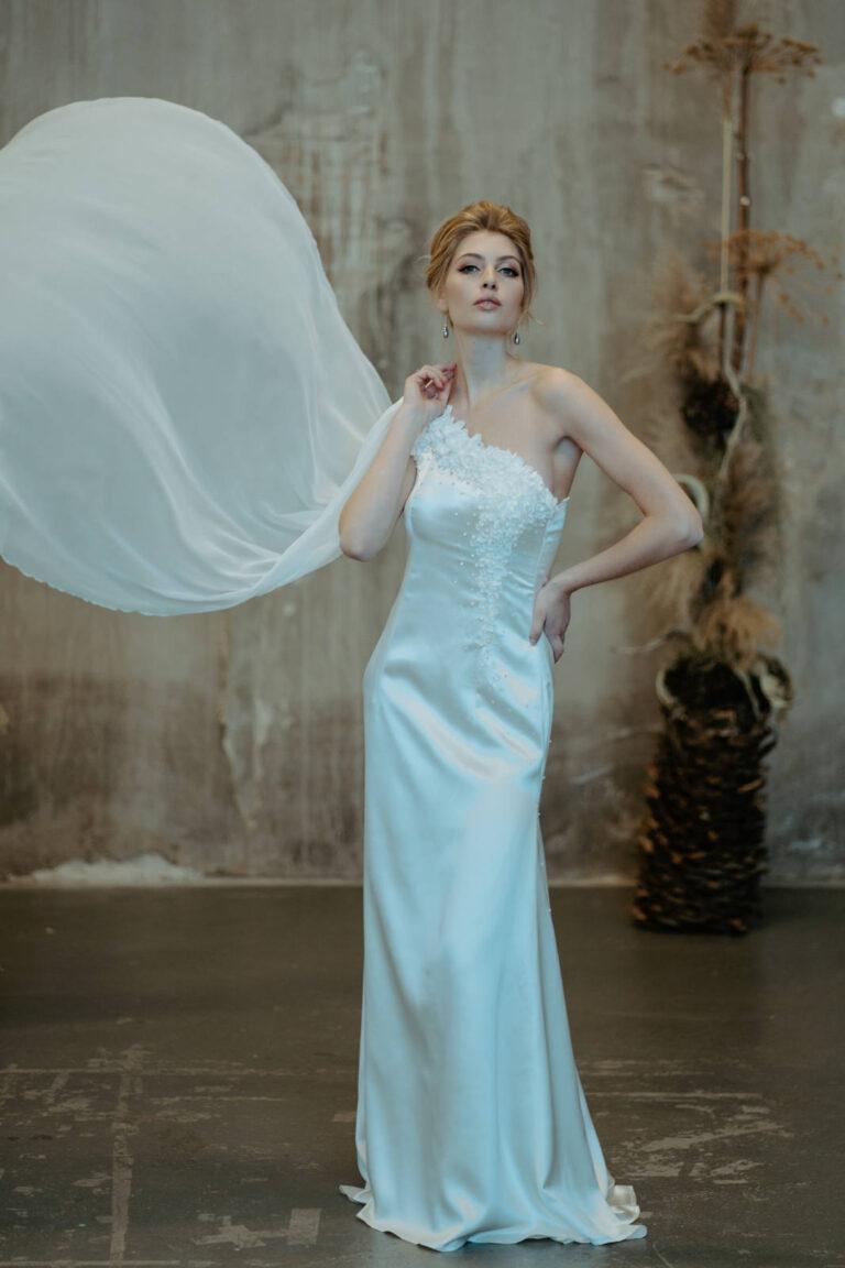 Smuk brudekjole med den fineste lange flæse som falder smukt ned over den ene skulder