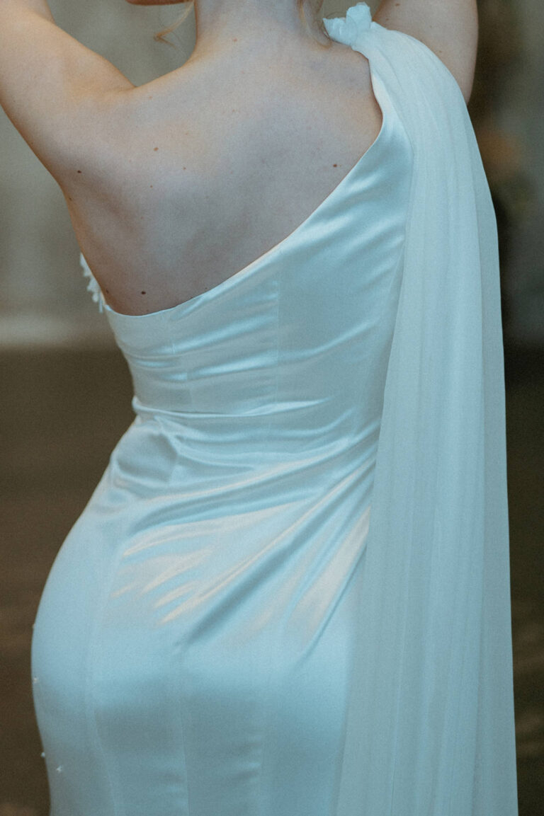 Smuk figursyet brudekjole med de fineste detaljer og lang flæse i silke som falder ned over skulder og ryg