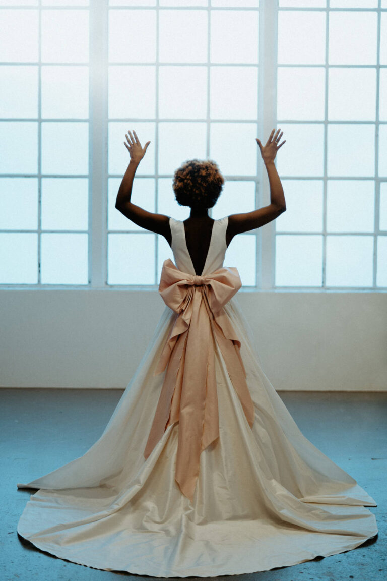 Brudekjole med dyb ryg og stor smuk rosa sløjfe bagpå kjolen