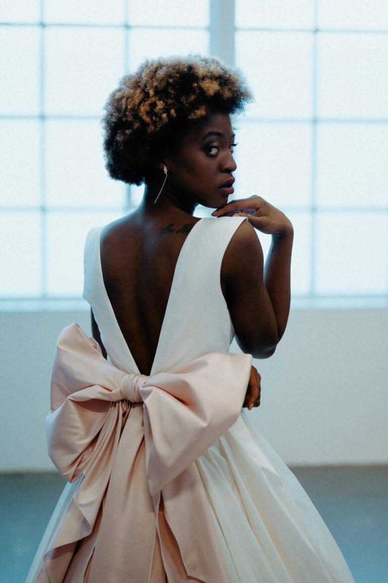 Brudekjole med dyb udskæring i ryggen med den store rosa sløjfe i ryggen