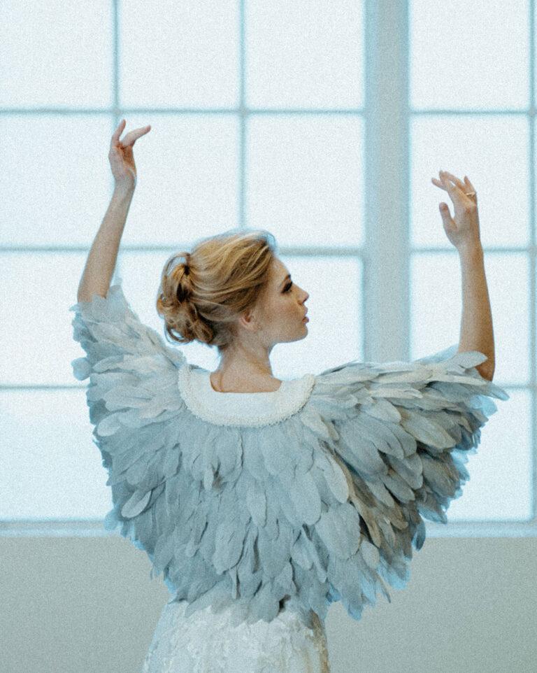ekstravagant kappe af isblå fjer, der fungerer som smukt tilbehør til brudekjolen
