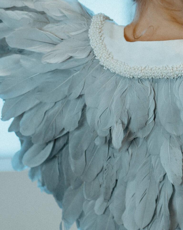 Smuk kappe med isblå fjer og smukke perler rundt i halsen, som fungerer perfekt til brudekjolen