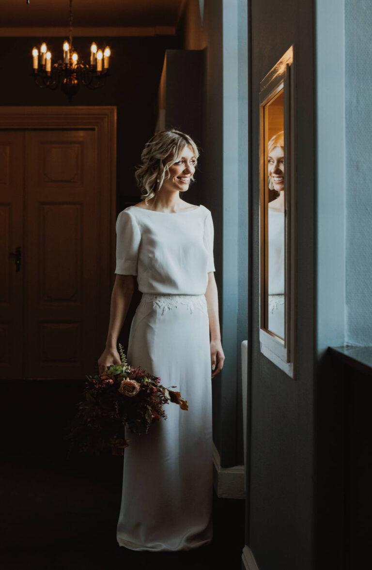 brudekjole med løstsiddende overdel i smukt crepe de chine-silkestof og et fint blondebælte i taljen
