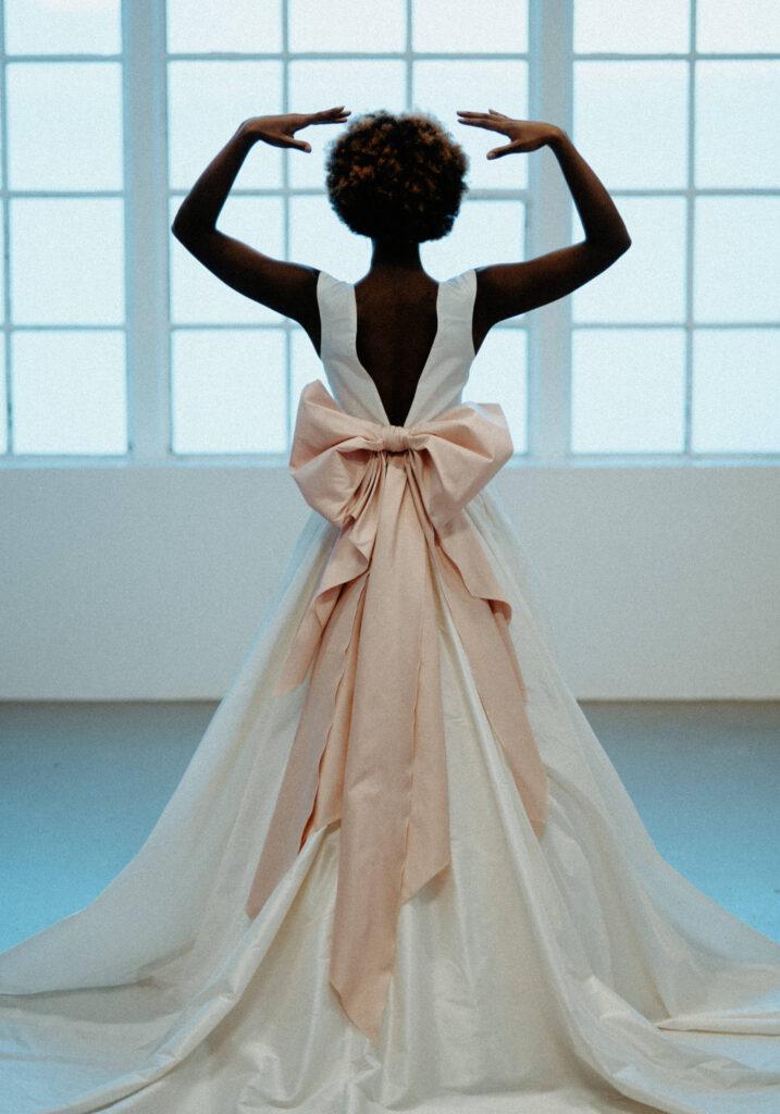 smuk elegant brudekjole med stort skørt og langt slæb med dyb ryg og stor lyserød sløjfe