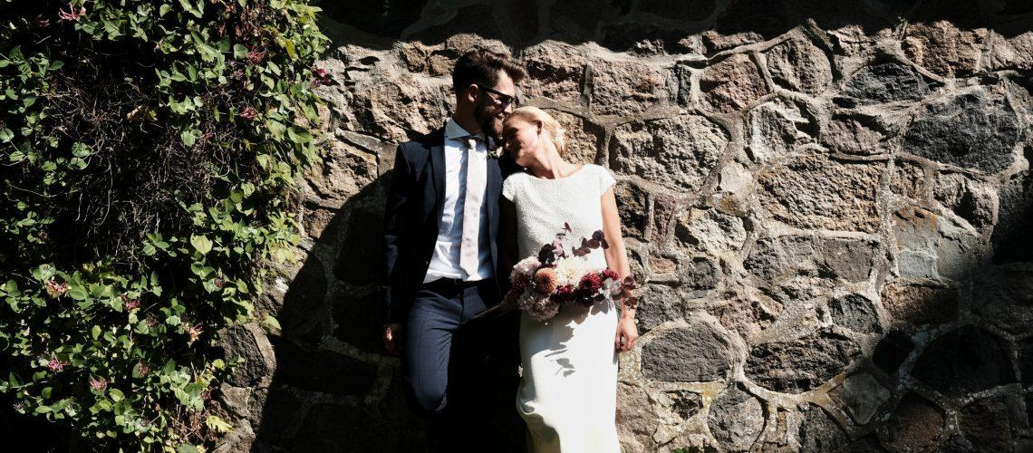 brud i smuk kjole med bådudskæring og korte ærmer ved stensætning i solskin